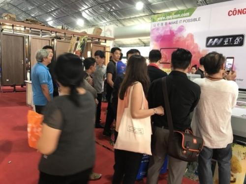 Khách hàng hào hứng tham quan gian hàng của Công ty MayInQuangCao